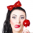 Sweet pin-up girl eating a candy toffee apple — Photo