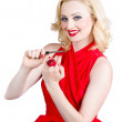 Blond pinup woman in red dress making manicure — Stock Photo