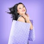 Smiling girl shopper holding purple shopping bags — Stock Photo #28511903
