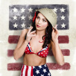 Foto de Stock  : USA pin-up woman. On vintage American flag wall
