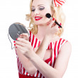 Stock Photo: Retro pin-up woman doing beauty make-up