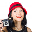 Smiling woman holding retro camera in hand — Stock Photo