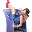 Happy woman in denim dress kicking back on chair — Stock Photo