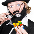 Stock Photo: Person Holding Eyeglasses Showing Cube Puzzle