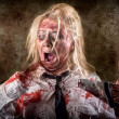 Dead female zombie with saw and amputated hand — Stock Photo