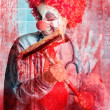 Stock Photo: Scary hospital clown cleaning blood smeared window
