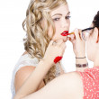 Make-up artist applying lipstick on a model — Stock Photo
