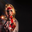 Evil female halloween zombie holding bomb — Stock Photo