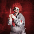 Stock Photo: Dr Death clown with big red hypodermic needle
