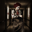 Dark hospital clown in spooky theatre nightmare — Stock Photo