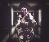 Creepy medical clown in grunge hospital hallway — Stock Photo