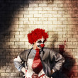 Stock Photo: Sinister gothic clown standing on grunge brickwall