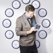 Photo: Time management business man looking at clock