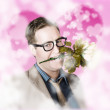 Funny romance nerd eyeing through love heart glass — ストック写真