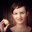 Stock Photo: Pretty young brunette womholding hatching egg