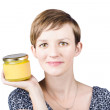 Stock Photo: Beautiful young womdisplaying jar of ghee