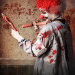 Stock Photo: Scary medical clown injecting horror into limb