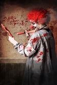 Scary medical clown injecting horror into limb — Stock Photo