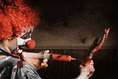 Evil Healthcare clown holding needle and syringe — Stock Photo