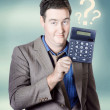 Photo: Business man holding calculator. Money question