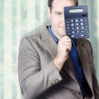 Photo: Business person hiding behind cash calculator