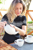 Pretty woman wearing a black sweater is pours a black tea — Stock Photo