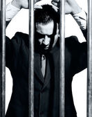 Man dressed in suit in jail behind prison bars — Stock Photo