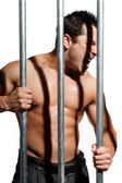 Sexy shirtless man behind bars on white background — Stock Photo