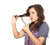 Beautiful girl with scissors cuts his dark wavy long hair — Stock Photo