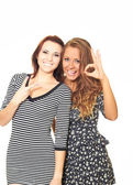 Two attractive smiling girls in dresses. The first girl showing — Stock Photo