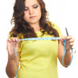 Attractive girl in a yellow shirt holding a scissors in her left — Stock Photo #12903397
