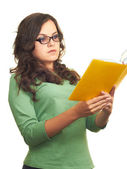 Attractive girl in a green shirt and glasses reading a yellow bo — Stock Photo