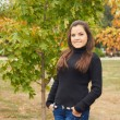 Stock Photo: Attractive smiling girl in black sweater standing under a tree i