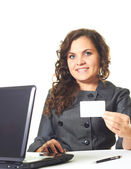 Attractive smiling girl in a gray dress works at the computer an — Stock Photo