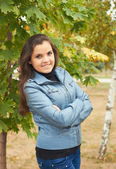 Attractive smiling girl in blue jacket standing under the tree i — Stock Photo