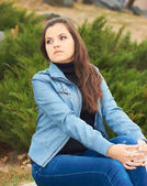 Attractive young girl in a blue jacket, sitting on a park bench — ストック写真