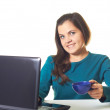 Attractive young smiling girl in a blue shirt working on laptop  — Stock Photo