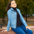 Attractive young girl in a blue jacket and blue jeans in the par — Stock Photo #13628658