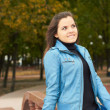 Attractive young girl in a blue jacket and blue jeans in the par — Stock Photo #13628667