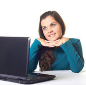 Attractive young smiling girl in a blue shirt working on laptop. — Stock Photo