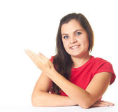 Attractive young smiling girl in a red shirt sitting at the tabl — Stock Photo