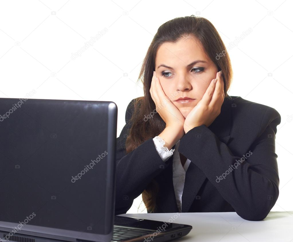 Depressed and tired business woman at work. A girl in a black jacket sitting at the table and working on the computer. Isolated on white background — Stock Photo #13628660