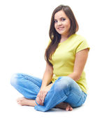 Attractive smiling young woman in a yellow shirt and blue jeans — Stock Photo