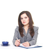 Attractive young woman in a gray blouse sitting at the table. Do — Stock Photo