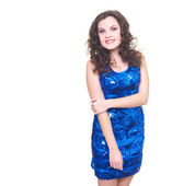 Attractive smiling young woman in a blue shiny dress slightly le — Stock Photo