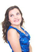 Attractive smiling young woman in a blue shiny dress looks into — Stock Photo