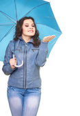 Attractive smiling young woman in a gray jacket standing under a — Stock Photo