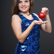 Happy young woman in a blue dress. Woman holds a red apple. — Stock Photo #21631099