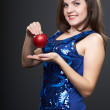Happy young woman in a blue dress. Woman holds a red apple. — Stock Photo #21631101