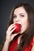 Attractive young woman in a red dress. Woman biting a red apple. — Stock Photo